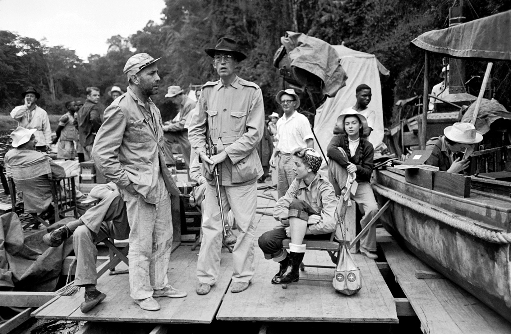 Bogart's wife - actress Lauren Bacall - seated next to Huston.