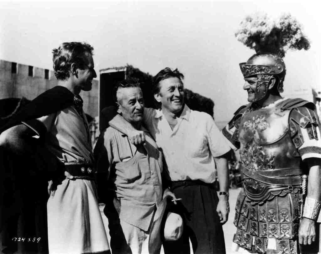 Kirk Douglas visits the set alongside Heston (left), Wyler (center) and Jack Hawkins (right)
