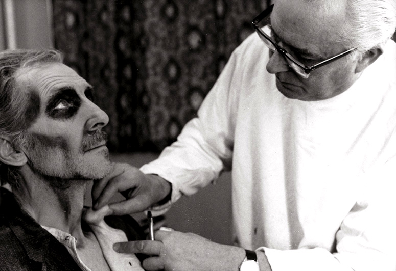 Make-up artist Roy Ashton, who created the look of some of Hammer's most memorable monsters, works on Peter Cushing's post-grave look. Picture via Empire Online.