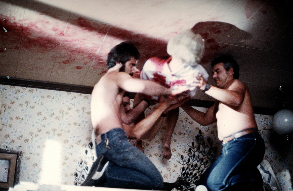 Two crew members prepare a stuntwoman for the shot in which Tina's body falls from the ceiling onto her bed in slow-motion.